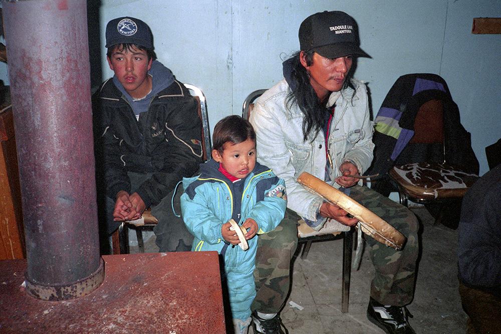Photo couleur d'un homme, d'un adolescent et d'un bambin regardant une partie de jeux de mains dénés. L'homme frappe un tambour en peau de caribou avec une baguette de bois. Le bambin tient son propre petit tambour.