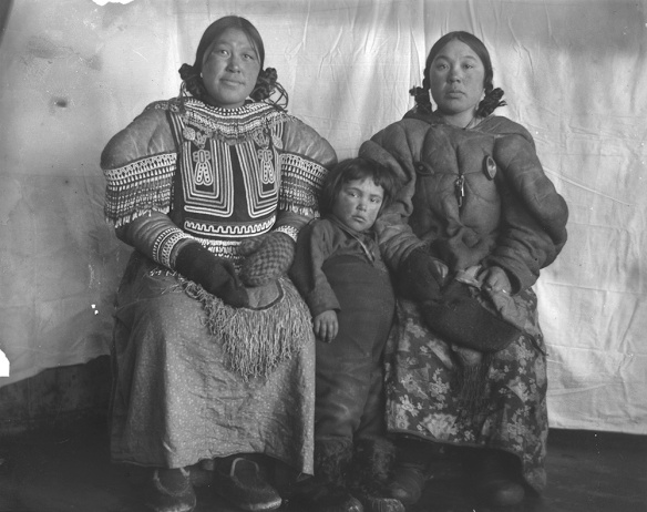 Photographie noir et blanc montrant deux femmes et un enfant vêtus de parkas devant une toile.