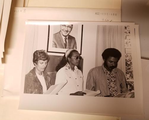 Photographie noir et blanc de trois jeunes assis à une table dans une salle de réunion, tenant des notes d'allocution ou des ordres du jour. À la gauche se trouve une femme blanche avec des cheveux courts et une veste en suède. Au centre, une femme noire porte des lunettes fumées et un large bandeau. À droite, un homme noir porte un chandail à motifs et une veste unie. Sur le mur derrière eux, au-dessus de leur tête, est accroché un grand portrait photographique d'un homme blanc âgé vêtu d'un veston et d'une cravate.