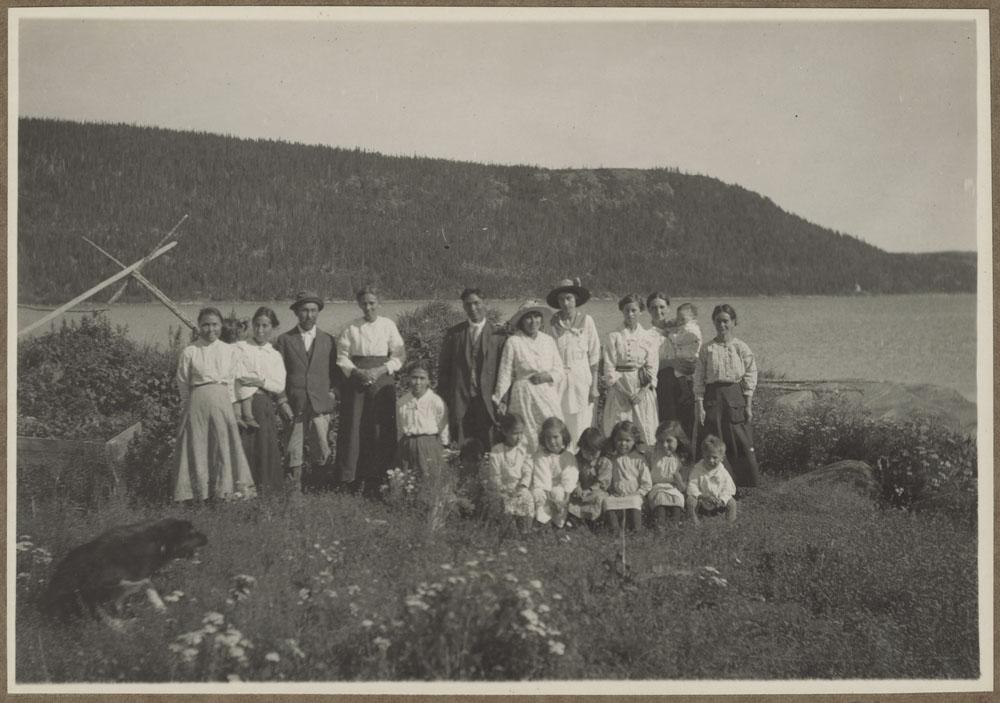 Photo noir et blanc d'un groupe d'hommes, de femmes et d'enfants assis ou debout dans un champ où poussent des fleurs. On voit derrière eux une étendue d'eau et des terres, au loin. Un chien se trouve à gauche dans l'avant-plan.