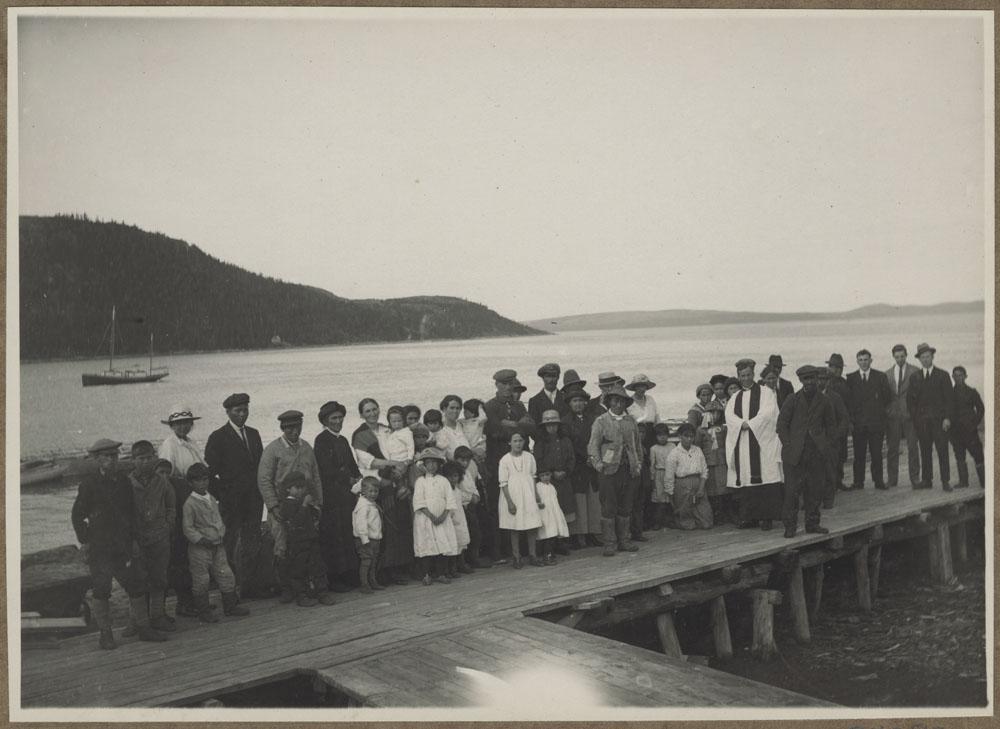 Photo noir et blanc d'un grand groupe d'hommes, de femmes et d'enfants sur un quai. On aperçoit au loin une étendue d'eau, un bateau et des montagnes.