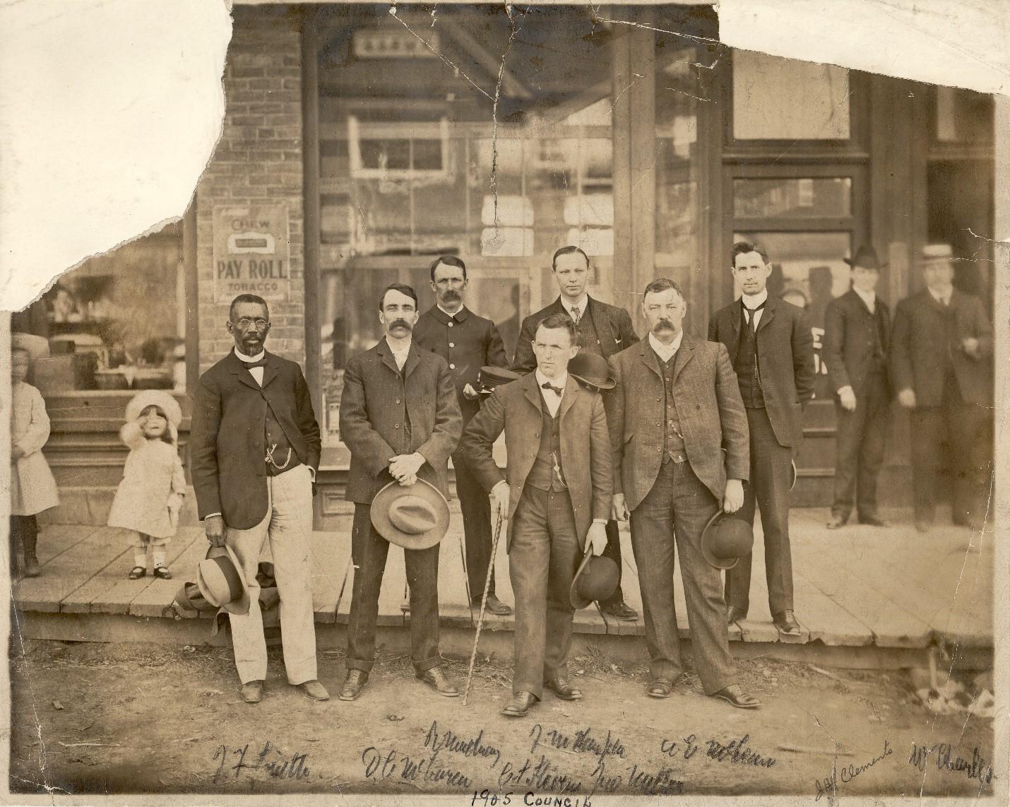 Photographie noir et blanc de sept hommes en complet prenant la pose sur un trottoir en bois devant l'entrée d'un bâtiment. À l'arrière-plan, on voit des passants – deux hommes en complet et deux jeunes filles inconnues vêtues de robes blanches et coiffées de chapeaux blancs.