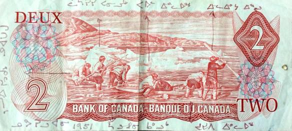 Photo couleur du verso d'un billet de banque canadien de 2 $ de 1975-1979, sur lequel les noms des six personnes qui y figurent sont inscrits en écriture syllabique.