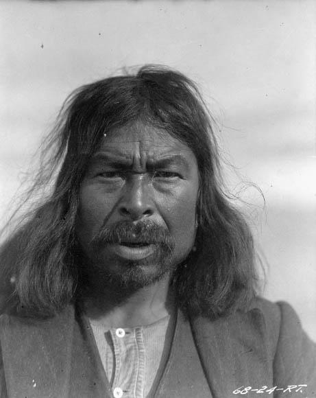 Photo noir et blanc d'un homme aux cheveux longs et portant une moustache.