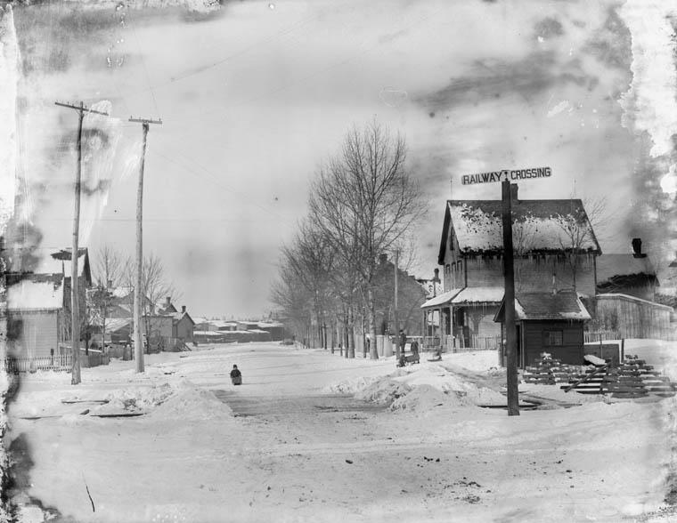 Photo noir et blanc d'une rue en hiver. On voit un panneau indiquant un passage à niveau, des maisons, des poteaux de ligne électrique et une personne qui pousse un toboggan au milieu de la rue.