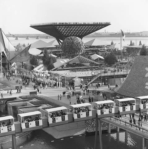 Photo noir et blanc de passants marchant entre de vastes pavillons au bord de l'eau. À l'avant-plan se trouve un train de voitures blanches.
