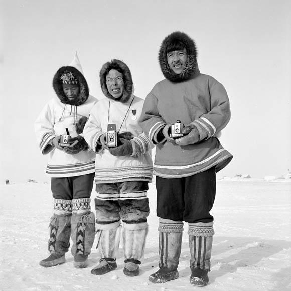 Photo noir et blanc de trois hommes inuit debout à l'extérieur pendant l'hiver. Ils portent tous des vêtements traditionnels.