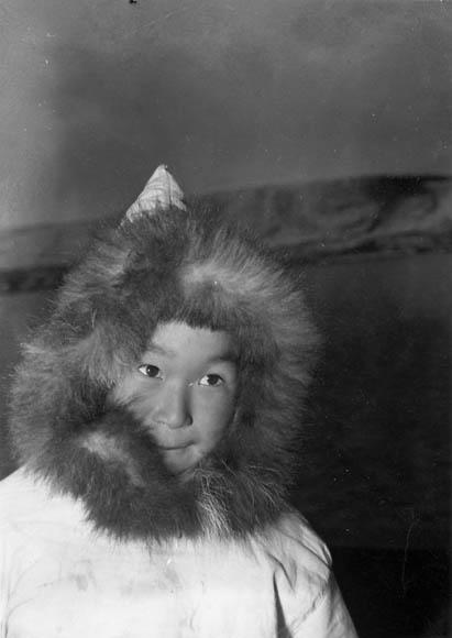 Photo noir et blanc d'un jeune garçon portant un capuchon bordé de fourrure.