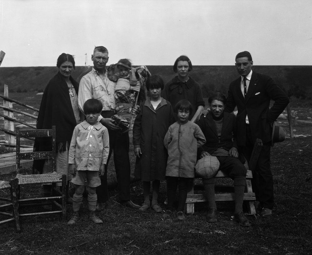 Photo noir et blanc de neuf personnes prenant la pose pour l'appareil. Un homme porte un enfant dans un tikinagan. On voit des broussailles en arrière-plan. Il n'y a aucun bâtiment à l'horizon.
