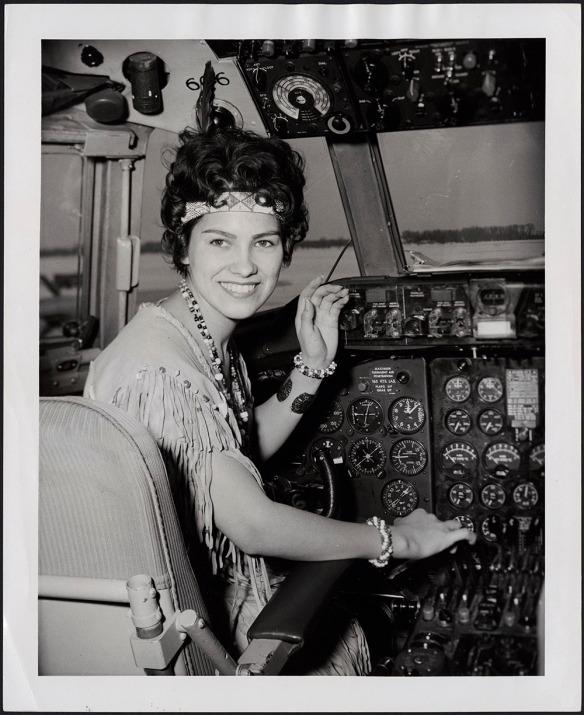 Photo noir et blanc d'une femme souriant à l'appareil. Elle porte un costume en peau de daim, un collier, des bracelets et un bandeau.