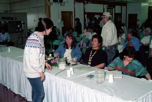 Photo couleur d'une femme debout vêtue d'un chandail blanc, en train de discuter avec trois femmes assises en face d'elle, de l'autre côté d'une longue table.