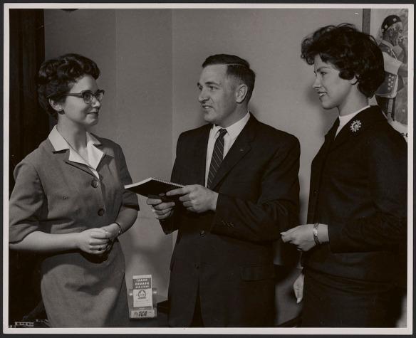 Photo noir et blanc de deux femmes et d'un homme en tenue de ville.