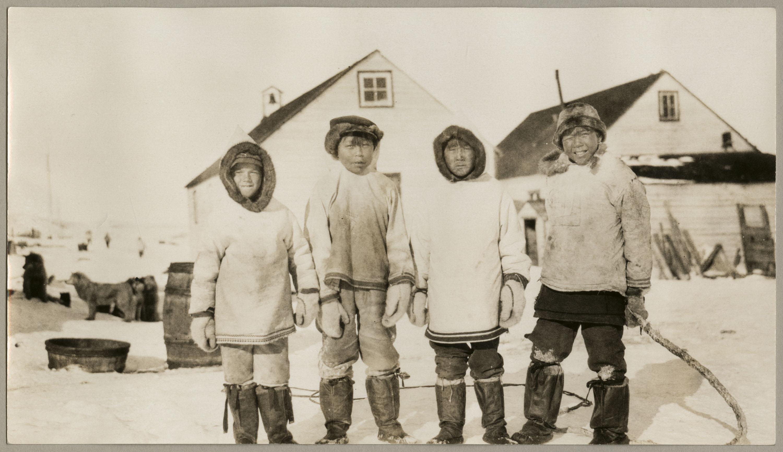 Photo noir et blanc de quatre garçons vêtus de parkas regardant vers l'appareil photo. Il y a deux bâtiments en arrière-plan.