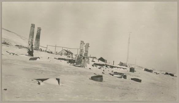 Photo noir et blanc des ruines d'un bâtiment avec des articles couverts de neige éparpillés un peu partout.