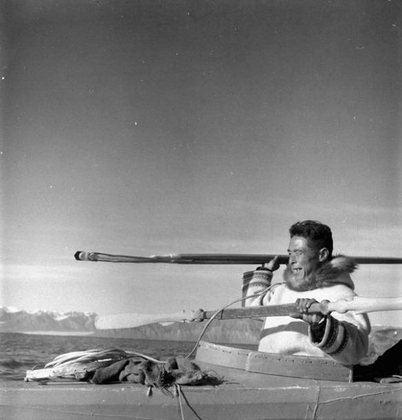 Photo noir et blanc montrant un homme assis dans un qajaq, sur le point de lancer un harpon. À l'arrière-plan, on aperçoit des montagnes enneigées.