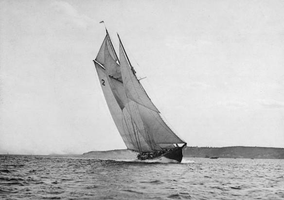 Photo noir et blanc de la goélette Bluenose à la ligne d'arrivée d'une course.