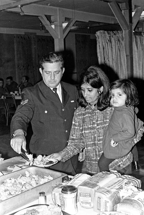 Photographie noir et blanc d'un homme en uniforme en train de servir de la nourriture à une femme qui porte un jeune enfant dans ses bras.