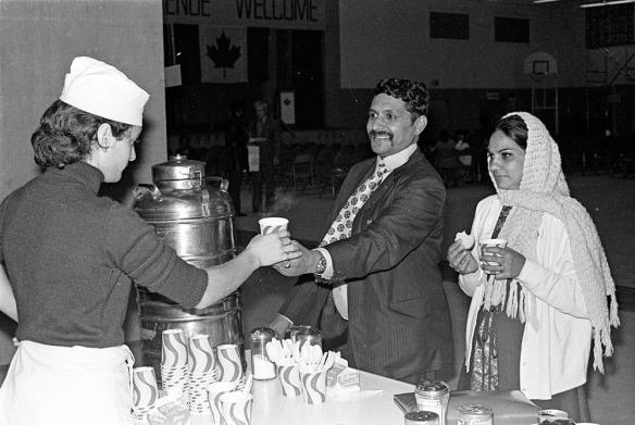 Photographie noir et blanc d'une femme portant un tablier et un calot de cuisine qui tend un verre en carton à un homme souriant en complet-veston, accompagné d'une femme portant un foulard et tenant un biscuit ainsi qu'un verre de carton.