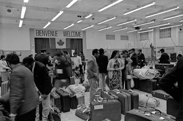Photo noir et blanc d'une grande salle relativement bondée. Des valises et bagages divers jonchent le sol. Sur le mur, un drapeau canadien est surmonté d'une banderole disant « Bienvenue, Welcome ».
