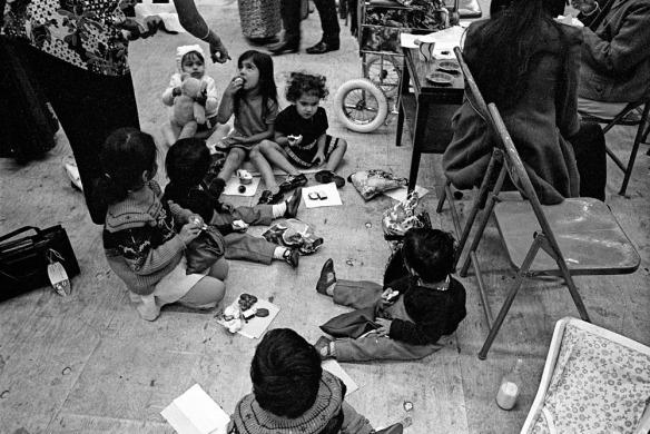 Photographie noir et blanc d'un groupe d'enfants en train de manger par terre.
