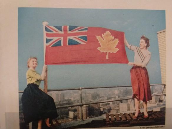 Photographie couleur de deux femmes tenant un drapeau sur le toit d'un édifice.