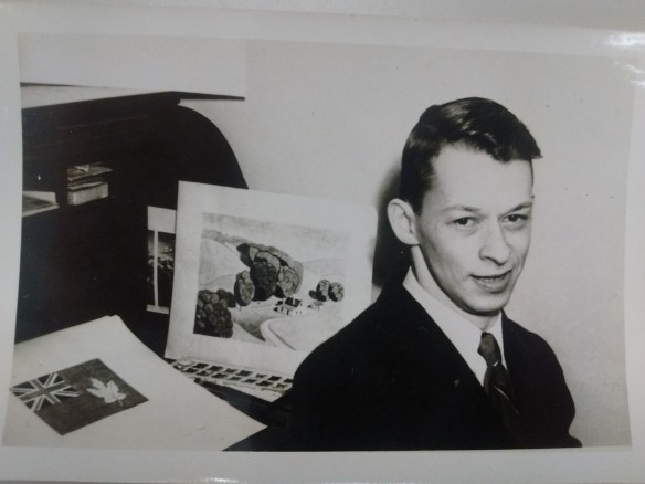 Photo noir et blanc d'un homme regardant l'objectif, près d'un dessin de son drapeau, visible en arrière-plan.