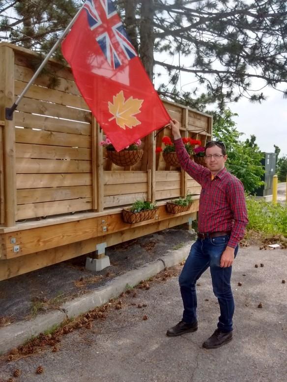 À l'extérieur, un homme en jeans et en chemise à carreaux rouge fait face à l'objectif, debout près d'un drapeau qu'il tient par le coin.