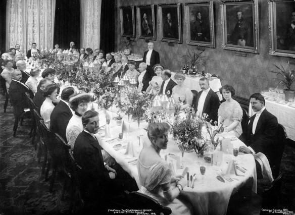 Photo noir et blanc de personnes en costume d'apparat assises autour d'une longue table ovale. La table comporte des couverts et des centres de table décoratifs.