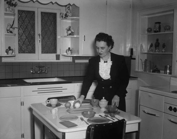 Photo noir et blanc d'une femme mettant la table dans une cuisine
