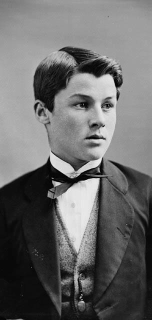 Photo noir et blanc d'un garçon vêtu d'un complet.