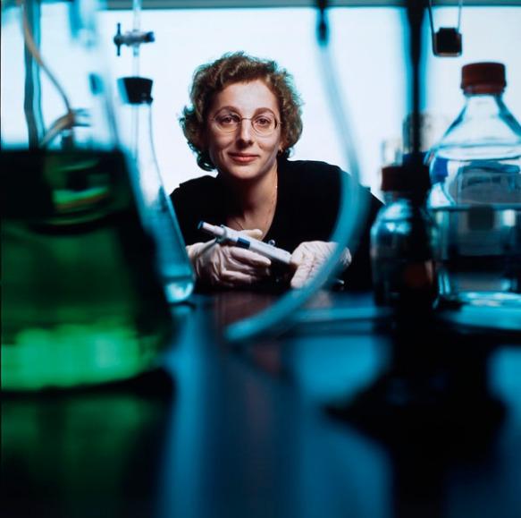 Photo couleur d'une femme avec des lunettes, face à l'objectif. On aperçoit des récipients et des bouteilles remplis de liquide à l'avant-plan.