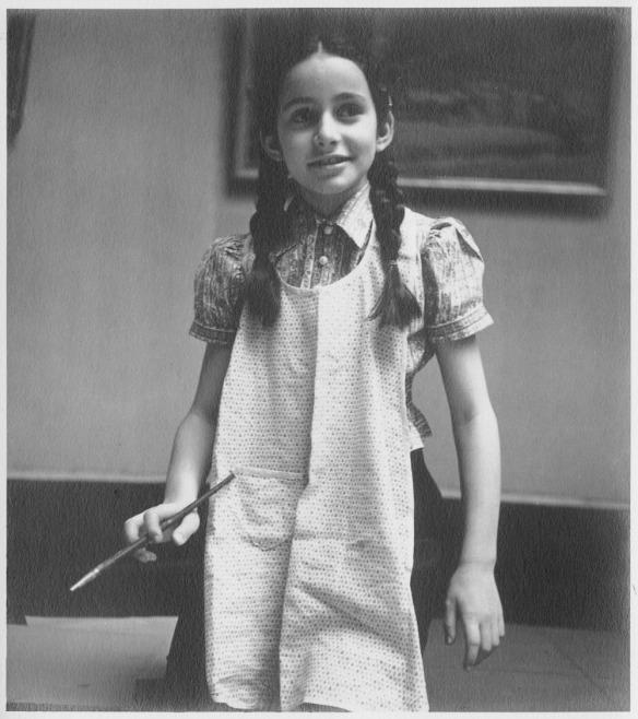 Photographie noir et blanc d'une jeune fille aux tresses noires vêtue d'un tablier pâle et agenouillée sur le plancher avec un pinceau dans la main droite. On peut voir le bas d'un tableau encadré derrière elle.