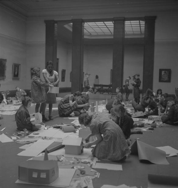 Photographie noir et blanc d'enfants agenouillés dans un musée d'art, au milieu du plancher, entourés de papier et de fournitures artistiques. Une enseignante debout au milieu de la pièce aide une élève. Les murs sont parsemés de peintures encadrées, et on peut voir une galerie adjacente derrière quatre colonnes foncées. De la scène émane l'énergie des enfants qui construisent des maisons en papier.