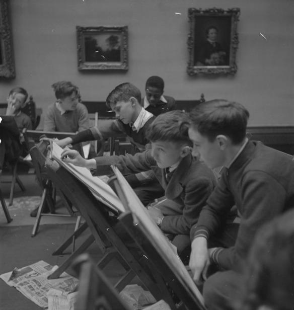 Photographie noir et blanc sur laquelle six garçons sont assis dans un musée d'art. Devant chacun d'eux, une chaise sert de chevalet. Deux toiles encadrées ornent le mur en arrière-plan et du papier journal recouvre le sol.