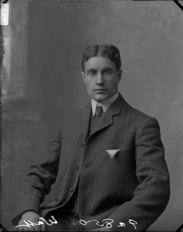 Photo noir et blanc d'un homme vêtu d'un complet foncé, face à l'objectif.