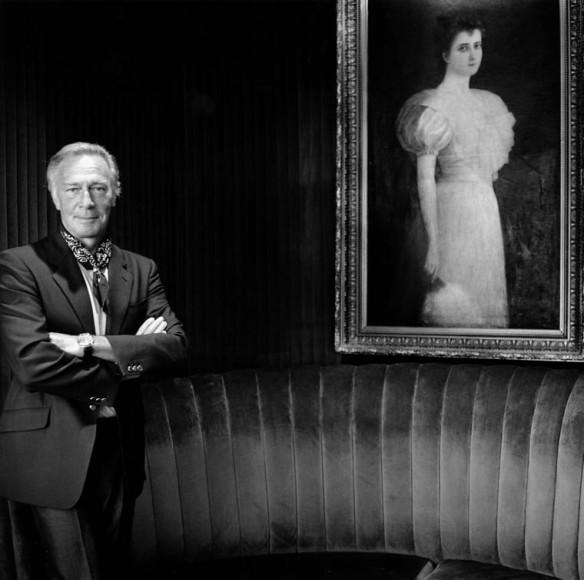 Photo noir et blanc de Christopher Plummer en complet, debout à gauche, avec les bras croisés. Une grande peinture encadrée, montrant une femme vêtue d'une robe et tenant un éventail, est accrochée sur la droite.