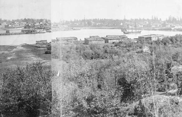 Photo noir et blanc de villages situés de chaque côté d'un port. Un grand navire vogue sur l'eau. Des forêts se trouvent derrière chaque village.