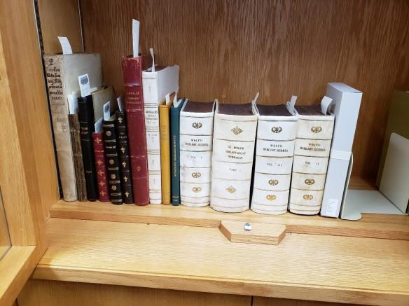 Photo couleur montrant des livres de différentes couleurs sur une étagère en bois. De petits morceaux de papier blanc dépassent du haut des livres.