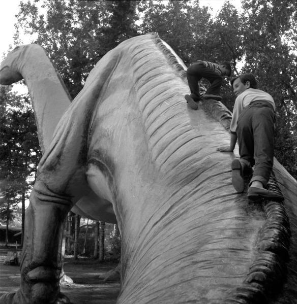 Photographie noir et blanc de deux enfants grimpant sur la sculpture d'un imposant dinosaure.