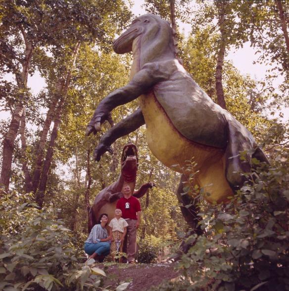 Une femme, un enfant et un homme sous l'imposante sculpture d'un dinosaure entourée d'arbres. Le groupe regarde un autre dinosaure.