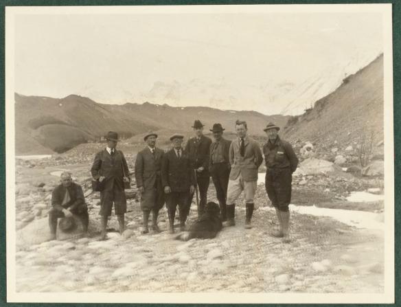 Photo noir et blanc d'un groupe d'hommes avec le mont Logan en arrière-plan.