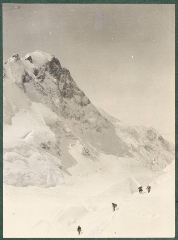 Photo du mont Logan avec quatre alpinistes en avant-plan.
