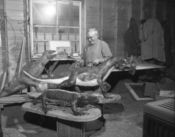 Un homme dans un garage ou un atelier, près de trois sculptures de reptiles préhistoriques. Il tient dans ses mains une canne de peinture et un pinceau.