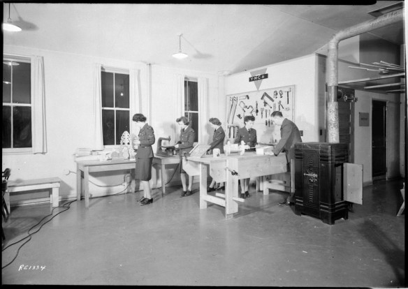 Photo noir et blanc d'un atelier avec trois grandes fenêtres. On y voit quatre femmes et un homme entourés d'outils, de tables et d'un établi. Un panneau au haut d'un mur indique « YMCA ».