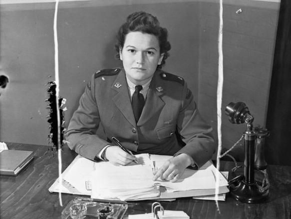 Photo noir et blanc d'une femme en uniforme militaire regardant l'objectif. Elle est assise derrière un bureau et tient un stylo dans sa main droite. Un téléphone de type chandelier est posé sur le bureau, à sa gauche.