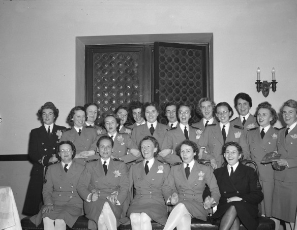 Photo noir et blanc d'un groupe de femmes en uniforme souriant à l'objectif. Deux des femmes portent un costume plus sombre. Celles au premier rang sont assises et se tiennent par la main. Les autres sont debout derrière; plusieurs se tiennent par le bras.
